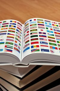 White encyclopedia resting on a stack of thick books lying on the floor. It is opened, showing two pages with the world flags and the names of the countries underneath them.